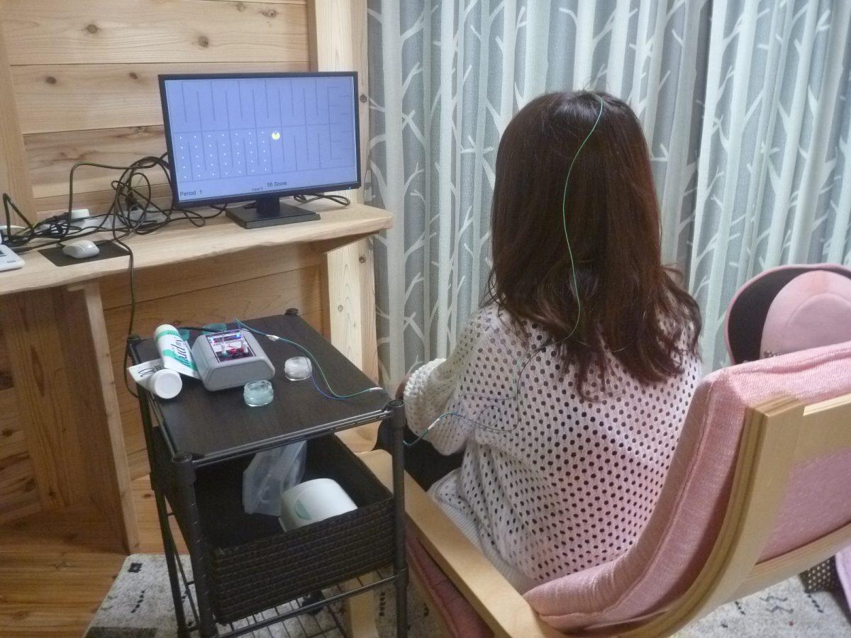 ニューロフィードバックトレーニングのゲームを行う少女